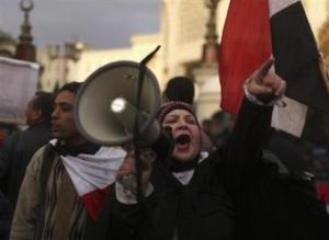 A protester uses a loudhailer as she chants anti-Mursi slogans during a protest in front of the presidential palace in Cairo